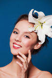Smiling natural woman with the lily flower on blue Stock Photo