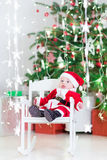 Smiling newborn baby boy in Santa costume under Christmas tree Royalty Free Stock Photo