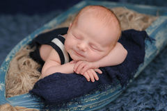Smiling Newborn Baby Boy Sleeping in a Boat royalty free stock images