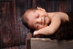 Smiling Newborn Baby Boy Sleeping in a Rustic Crate stock photos