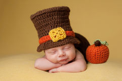 Smiling Newborn Baby Boy Wearing a Pilgrim Hat. Smiling four week old newborn baby boy wearing a crocheted Pilgrim hat. He is sleeping on a gold blanket next to