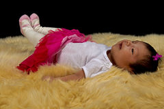 Smiling newborn Baby girl on a plush fur rug. A beautiful Hispanic newborn baby girl at 9 weeks old, smiles as she lays on a deep white fur against a black Royalty Free Stock Photos