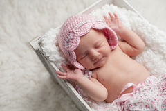Smiling Newborn Baby Girl Wearing a Pink Bonnet Stock Photo
