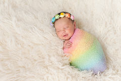 Smiling Newborn Baby Girl Wearing a Rainbow Colored Swaddle