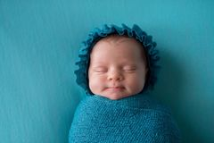 Smiling Newborn Baby Girl Wearing a Turquoise Blue Bonnet royalty free stock image