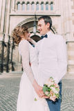 Smiling newlywed couple dancing and hugging near old gothic christian cathedral Stock Photography