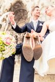 Smiling newlywed couple holding bouquet ball and high heels. Sitting outside the church stock image