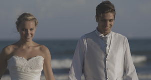 Smiling newlyweds running on the beach stock footage