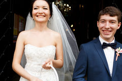 Smiling newlyweds stand in the front of the church Royalty Free Stock Photos