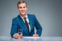 Smiling newsman holding a glass of water Royalty Free Stock Photo