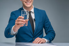 Smiling newsman holding a glass of water Royalty Free Stock Photos