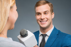 Smiling newsman taking an interview Stock Photos