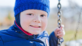 Smiling nice boy on a swing Stock Photos