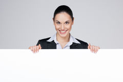 Smiling nice businesswoman holding blank poster. Stock Photos