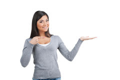 Smiling nice Indian woman pointing on copy space above her hand. Royalty Free Stock Image