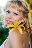 Smiling nice woman with yellow lily Stock Image