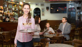 Smiling nippy and bar crew. Smiling nippy with beverages and bar crew at background Royalty Free Stock Photography