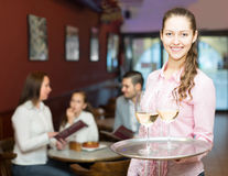 Smiling nippy and bar crew. Smiling nippy with beverages  on tray and bar crew at background Stock Image