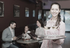 Smiling nippy and bar crew. Cheerful nippy with beverages and bar crew at background Royalty Free Stock Images