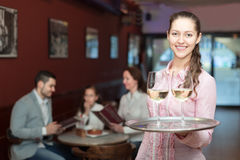 Smiling nippy and bar crew. Cheerful nippy with beverages and bar crew at background Royalty Free Stock Image