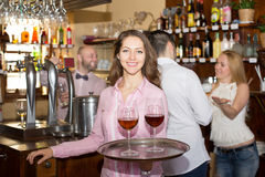 Smiling nippy with beverages. Happy smiling nippy serving bar guests with beverages Stock Photo