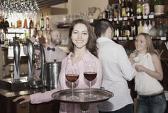 Smiling nippy with beverages. Smiling nippy serving bar guests with the beverages Stock Photo