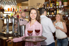Smiling nippy with beverages. Smiling nippy serving bar guests with the beverages Stock Photos