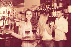 Smiling nippy with beverages. Smiling nippy serving bar guests with a beverages Stock Image