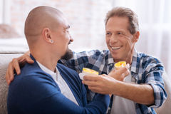Smiling non-traditional couple feeding each other with cupcakes Stock Images
