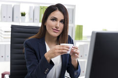 Smiling and nostalgic businesswoman with a cup of coffee in an o Stock Photography