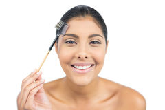 Smiling nude brunette using eyebrow brush Royalty Free Stock Image
