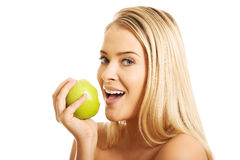 Smiling nude woman eating an apple Royalty Free Stock Photos