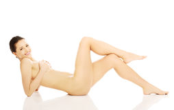 Smiling nude woman lying and holding her breast Royalty Free Stock Photos