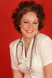 Smiling nurse. Smiling health care worker on red backdrop Royalty Free Stock Photo