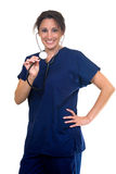 Smiling nurse. Confident Hispanic woman healthcare worker wearing dark blue scrubs holding the end of a stethoscope on white Stock Photo
