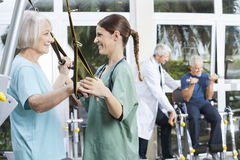 Smiling Nurse Assisting Senior Woman With Resistance Band Exerci Stock Photo