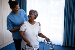 Smiling nurse assisting senior woman in walking with walker stock images