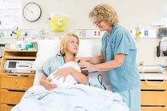 Smiling Nurse Assisting Woman In Breast Feeding Royalty Free Stock Photo