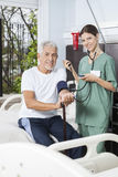 Smiling Nurse Checking Blood Pressure Of Patient In Rehab Center Stock Photos