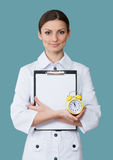 Smiling nurse with a clock Royalty Free Stock Photos