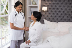 Smiling nurse comforting female patient on bed Royalty Free Stock Images