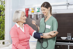Smiling Nurse Examining Blood Pressure Of Senior Patient Royalty Free Stock Photo