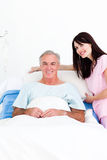 Smiling nurse fixing a senior patient's bed. In a hospital Stock Images