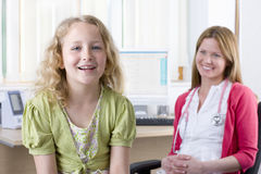 Smiling nurse and girl smiling in doctor's office Royalty Free Stock Photos