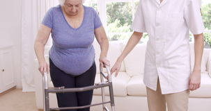 Smiling nurse helping senior woman walking