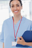 Smiling nurse holding files and looking at camera Stock Image