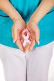 Smiling nurse holding pink breast cancer awareness ribbon. Royalty Free Stock Photo