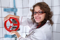 Smiling nurse holding red valve. Smiling nurse with curly hair holding red valve Stock Photos