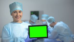 Smiling nurse holding tablet PC with green screen during operation, hospital ad