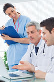 Smiling nurse listening to doctors talking about something on th Stock Images